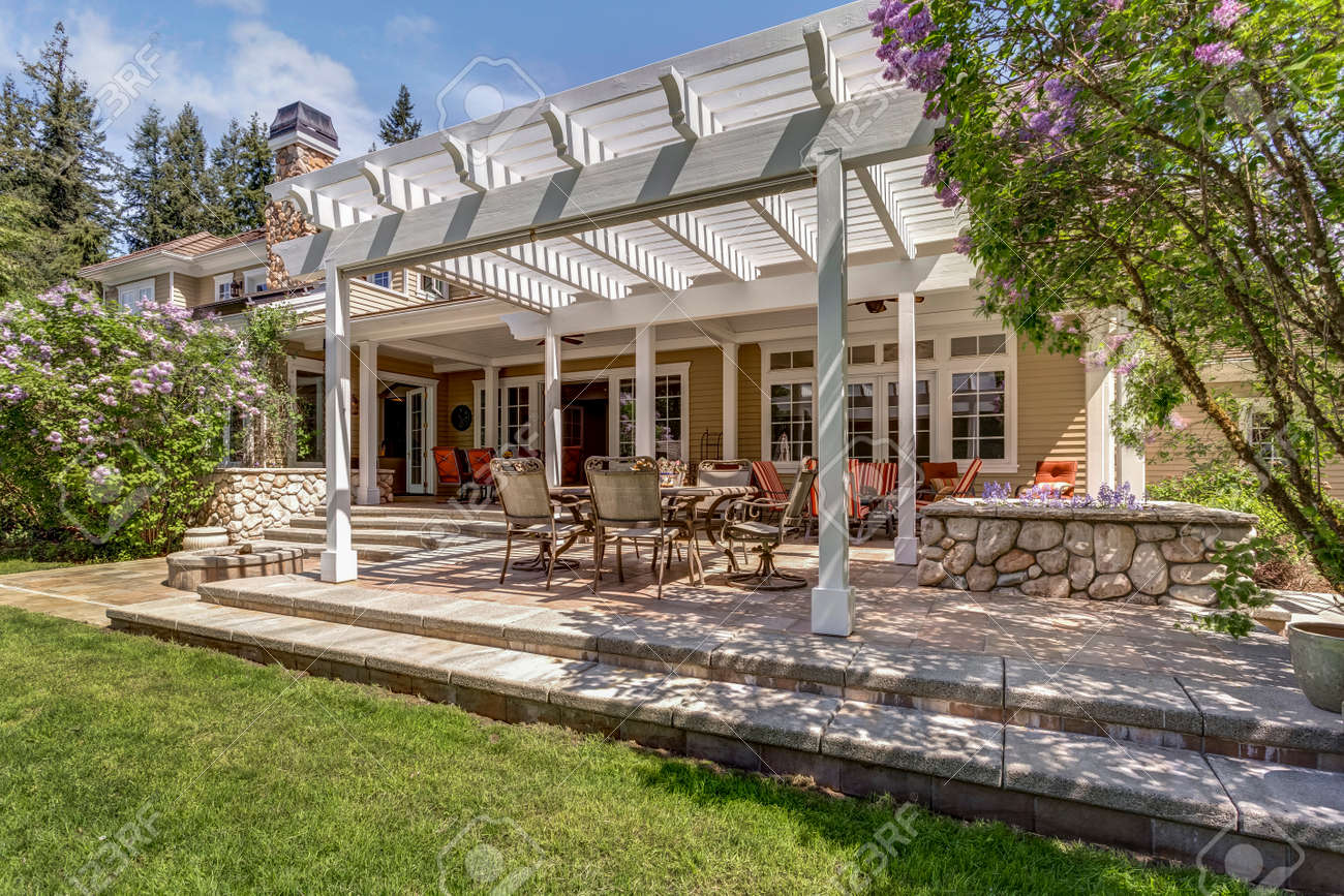 Lovely outdoor deck patio space with white dining pergola in the backyard of a luxury house. - 108106237