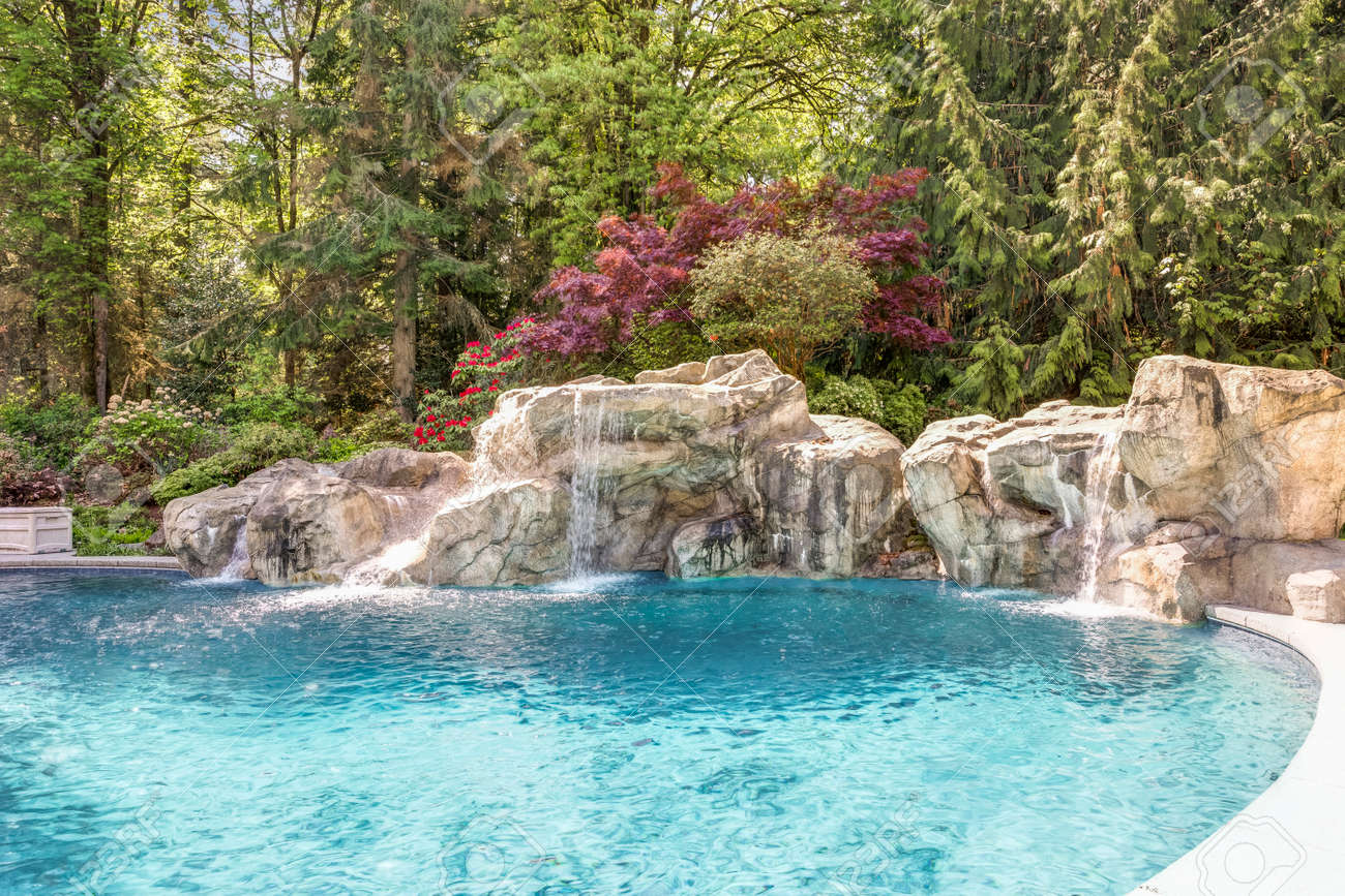Beautifully landscaped backyard showcases an expansive pool decorated with stone. - 108106238