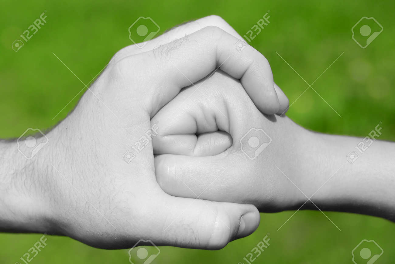 Black and white hand holding or stopping a fist in frot of green background stock photo