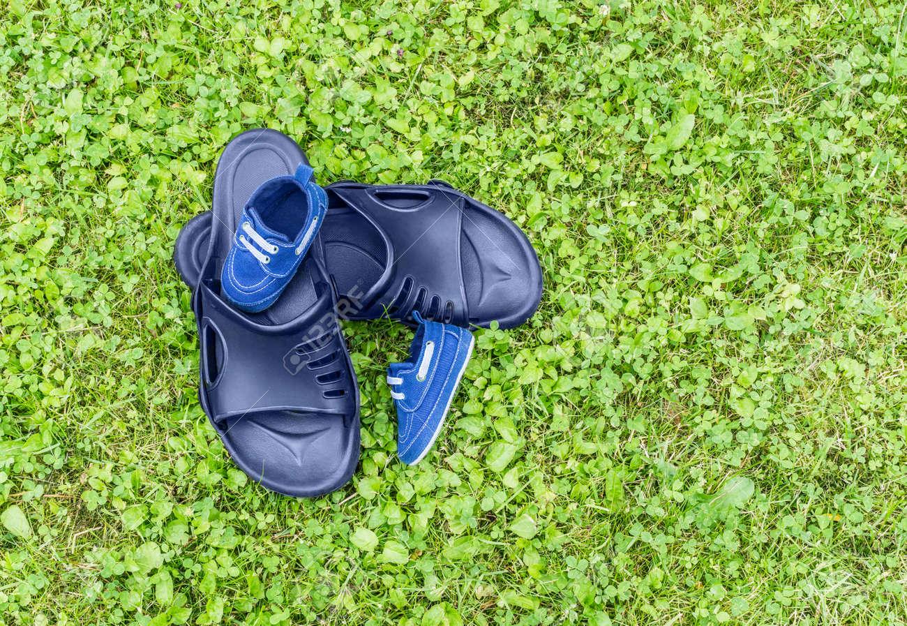 3067531f3 Foto de archivo - Las zapatillas de goma para hombres y los zapatos para  niños están en el césped. Vista desde arriba