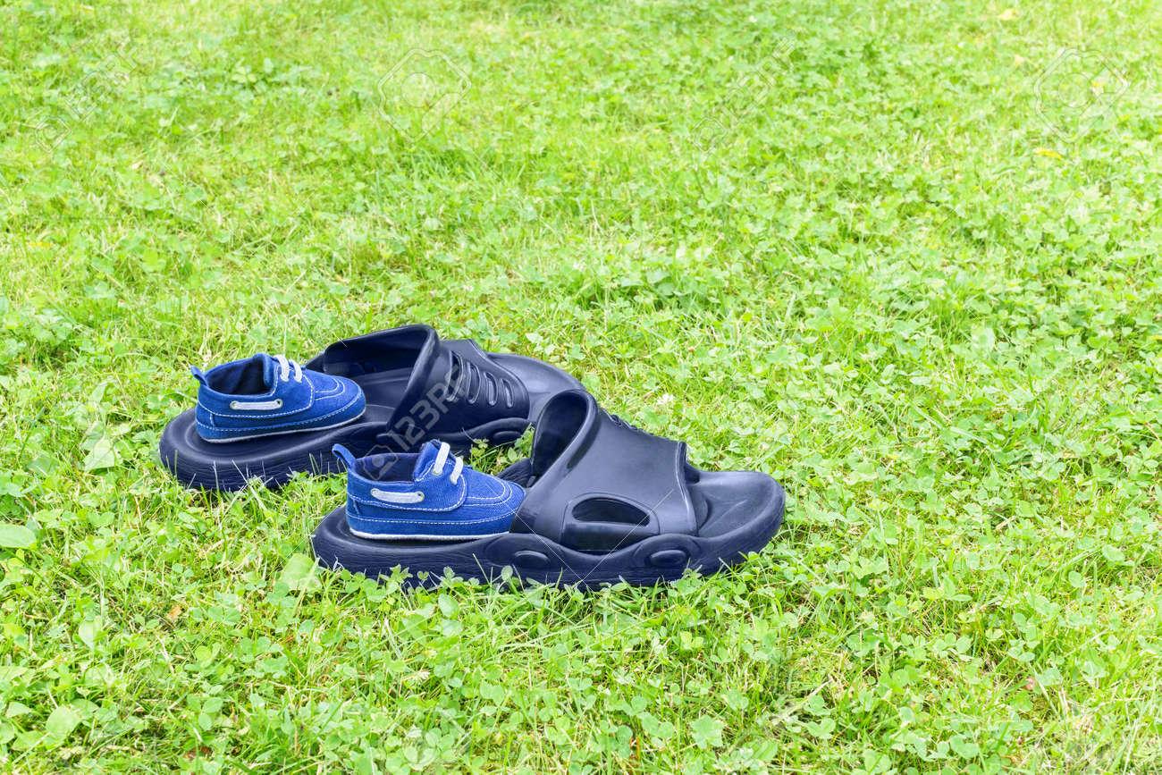 94b0cbd99 Foto de archivo - Las zapatillas de goma para hombres y los zapatos para  niños están en el césped