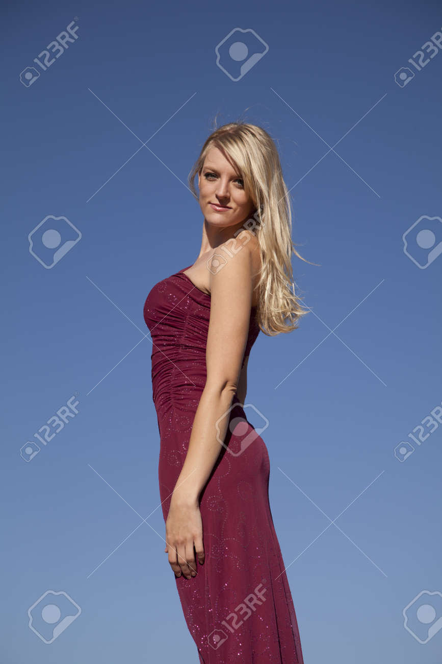 A Woman In Her Formal Red Dress Against The Blue Sky With A Serious
