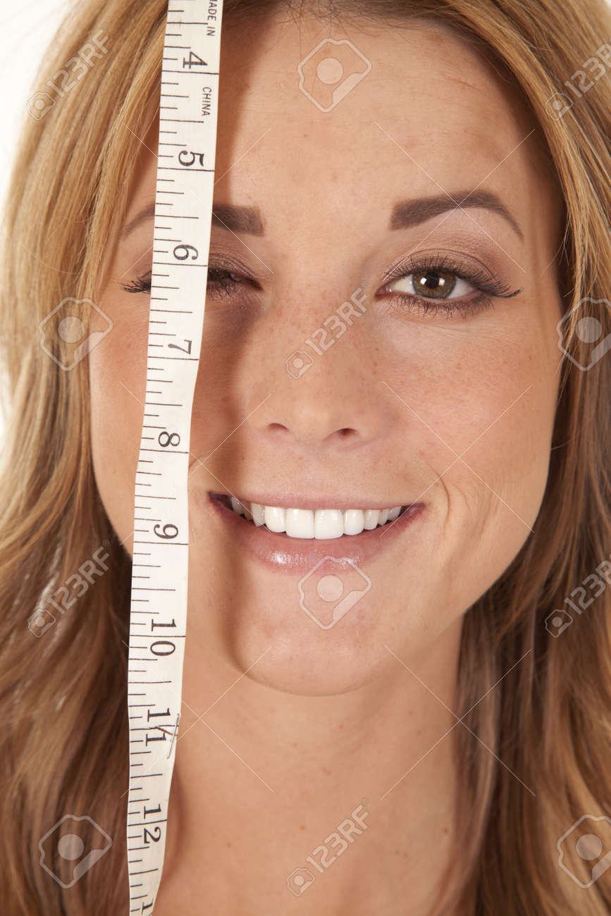 A woman with a measuring tape over one of her eyes with a smile on her face. Stock Photo - 12104352