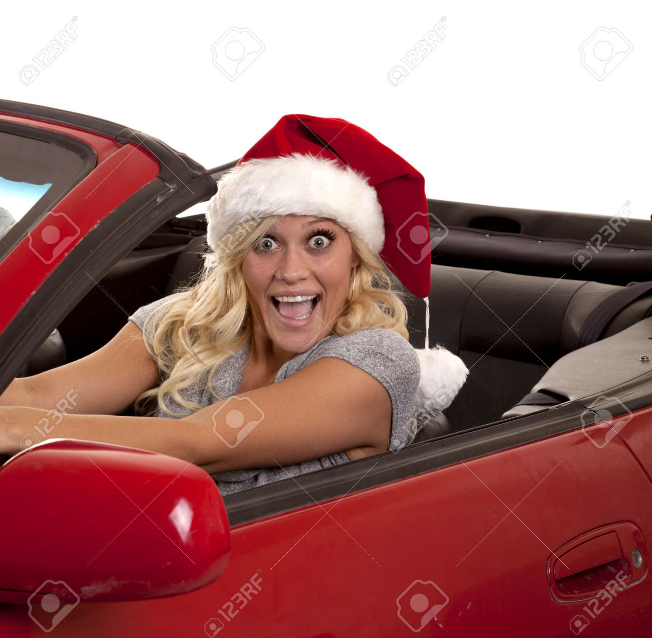 A woman with a very excited expression on her face driving while she is wearing her Santa hat. Stock Photo - 12104492