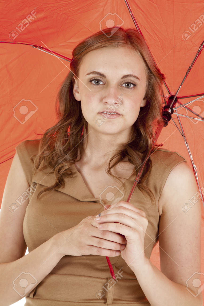 A close up of a woman holding on to a red umbrella with a small smile on her lips. Stock Photo - 14610685