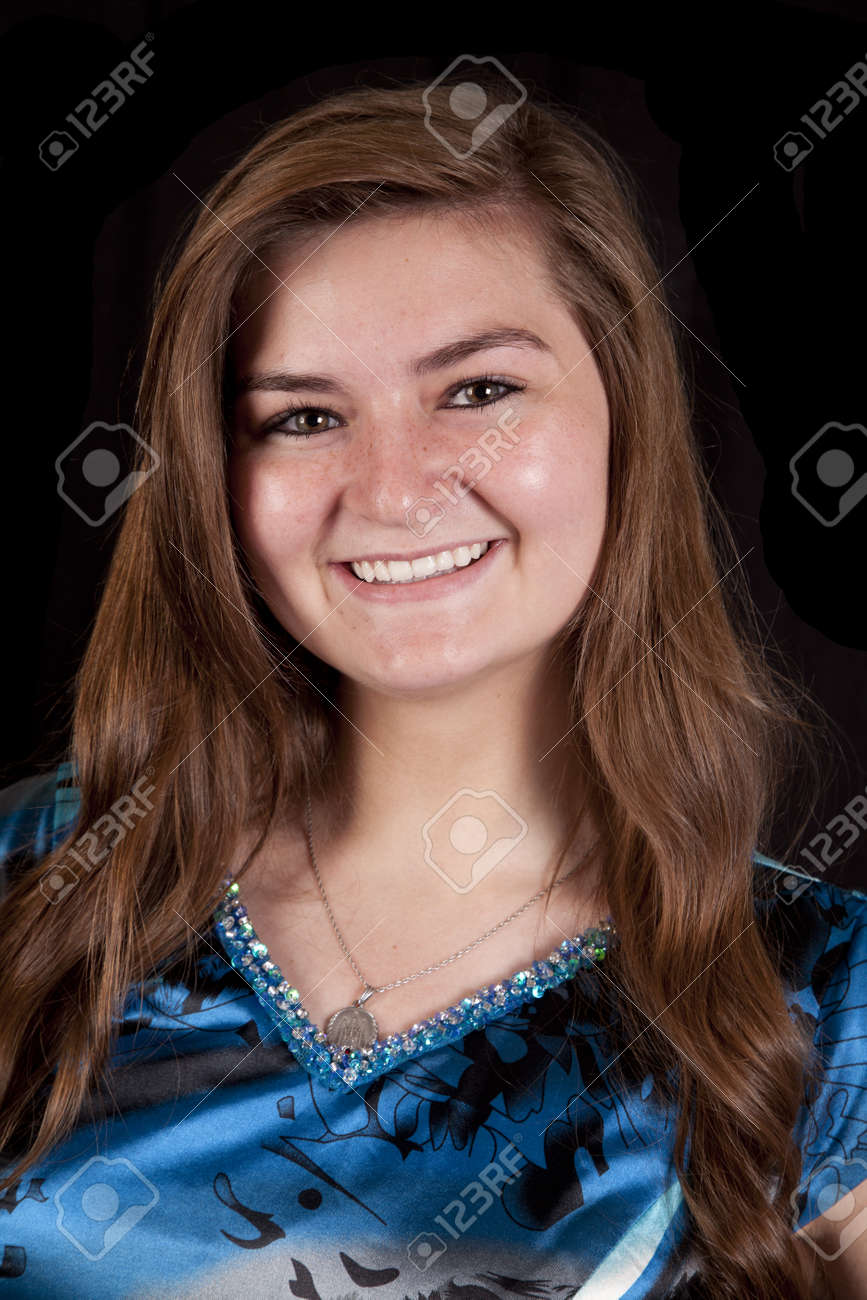 A teen girl with a big smile on her lips in her blue dress. Stock
