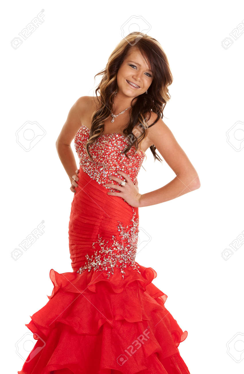 A teen girl in her formal dress posing with a smile on her face. Stock