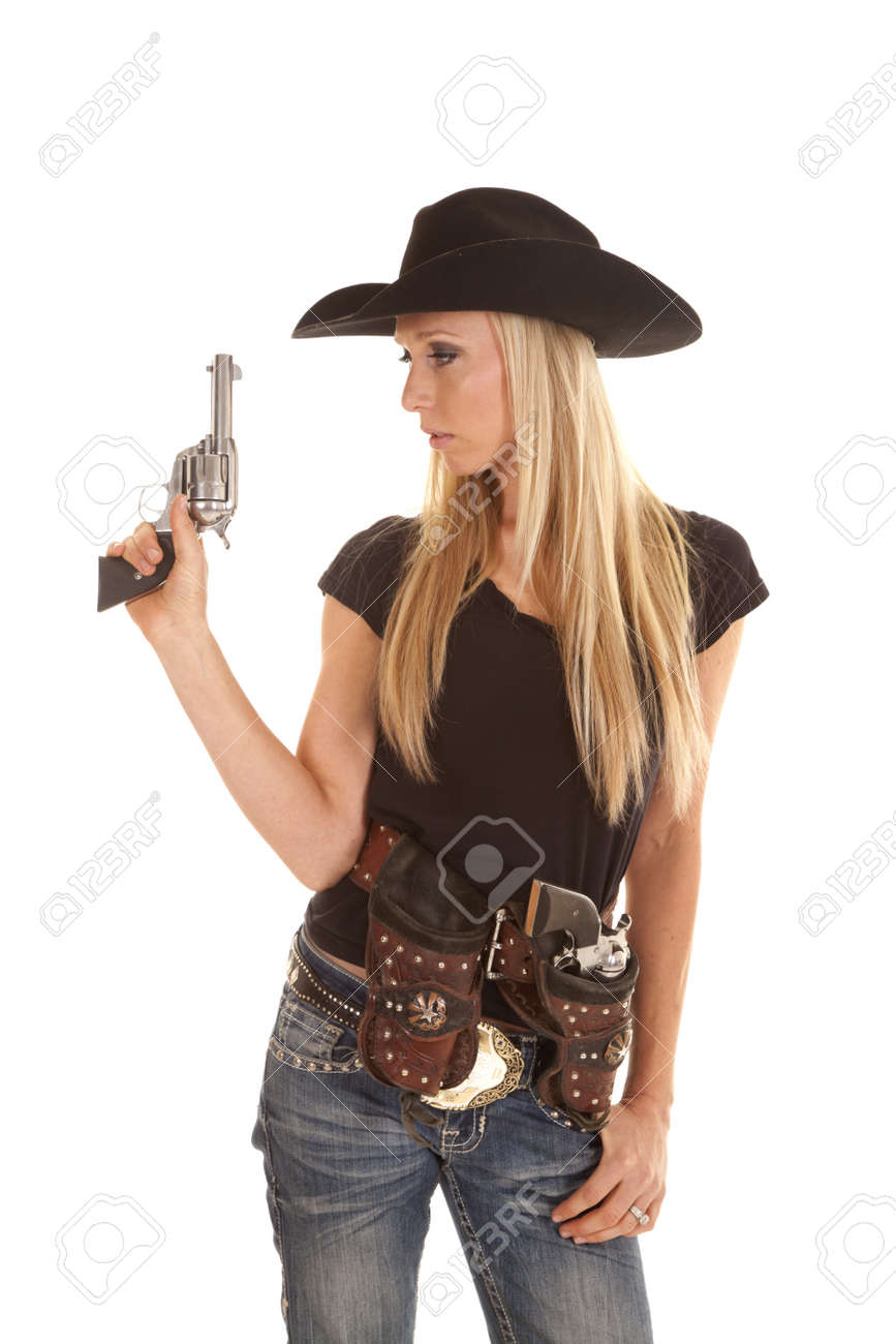 a cowgirl dressed in black holding up her pistol with her other gun in her holster. Stock Photo - 15726798
