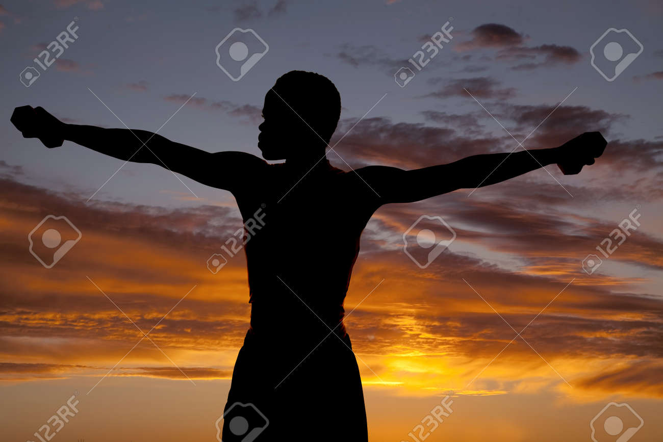 A silhouette of a man working out in the outdoors with weights Stock Photo - 15849510