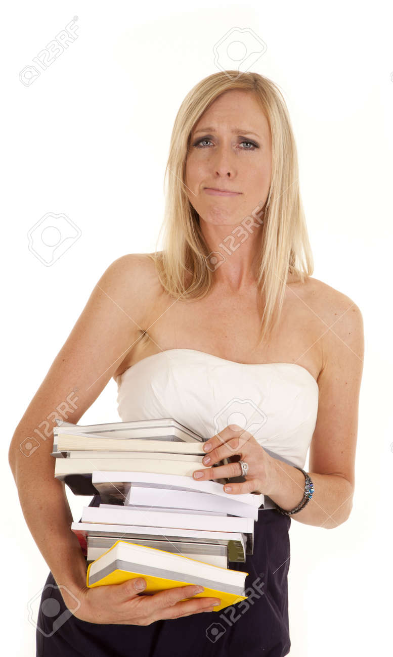 A woman blowing hair off of her face holding on to a stack of books. Stock Photo - 15849495