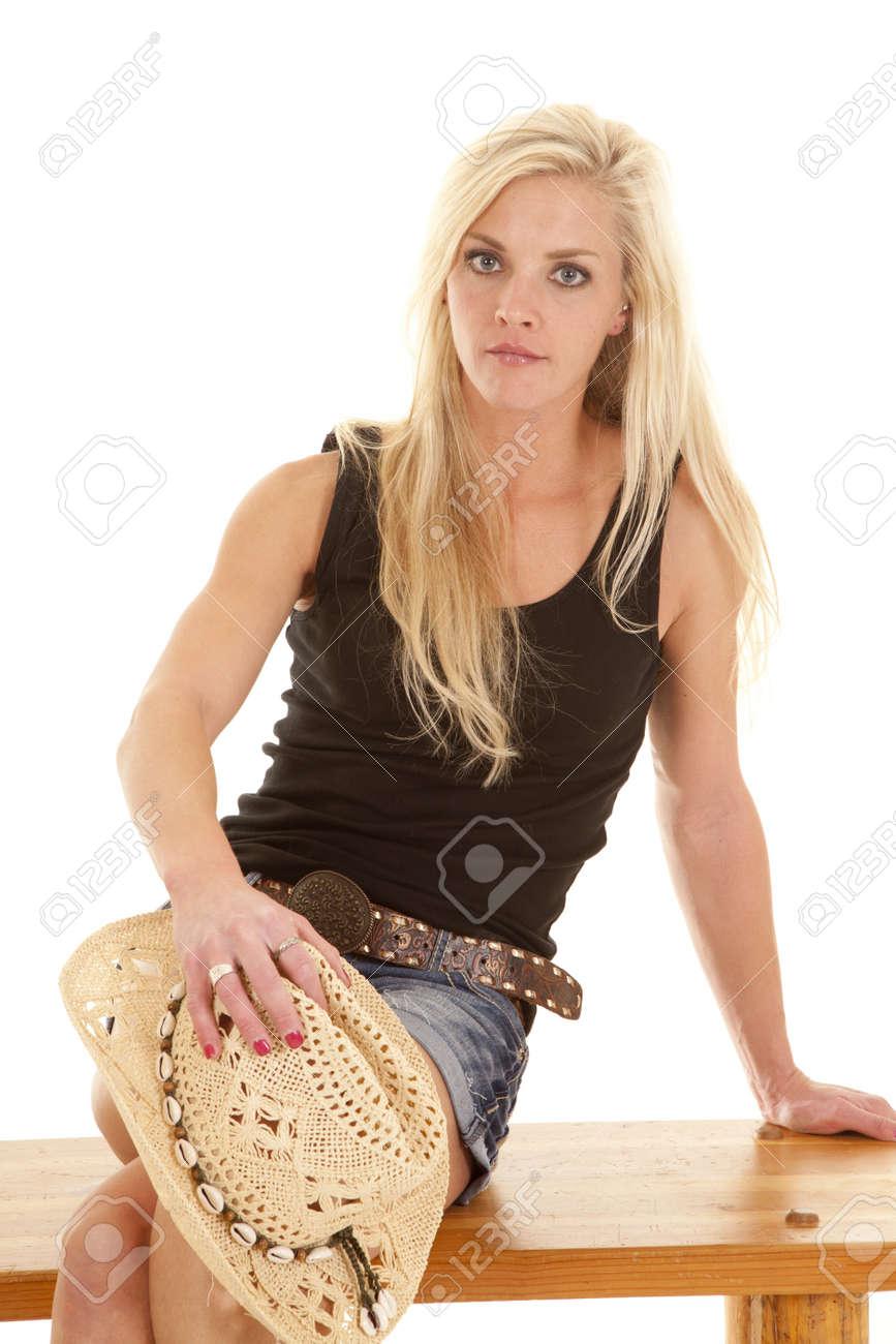 Foto de archivo - Una mujer está sentada en un banco con un sombrero de  vaquero en su rodilla. 3295ffeb1550