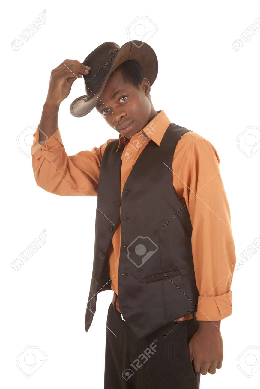 a man in his orange shirt and black vest putting on his cowboy hat. Stock Photo - 16035246
