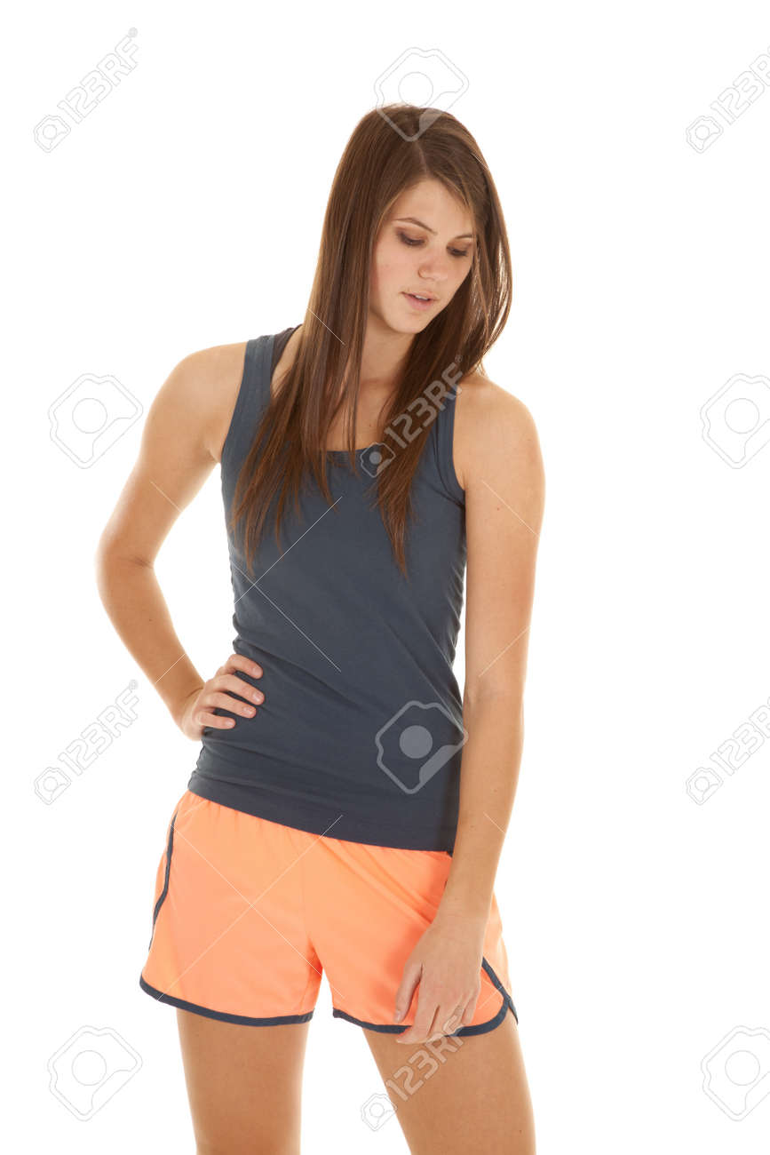 A woman in her fitness clothes looking down with a serious expression on her face. Stock Photo - 18187082
