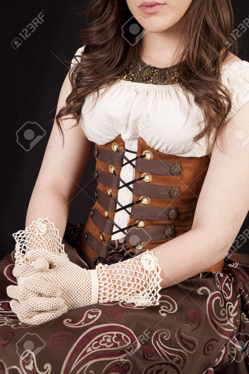 A Woman In Her Vintage Western Dress With Her Hands In Her Lap ...
