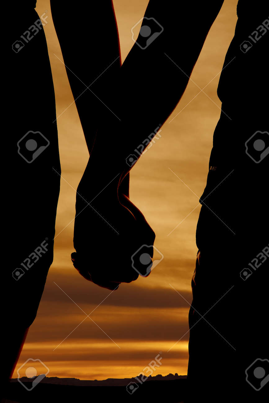a close up of a silhouette of a couple holding hands stock photo 20549156