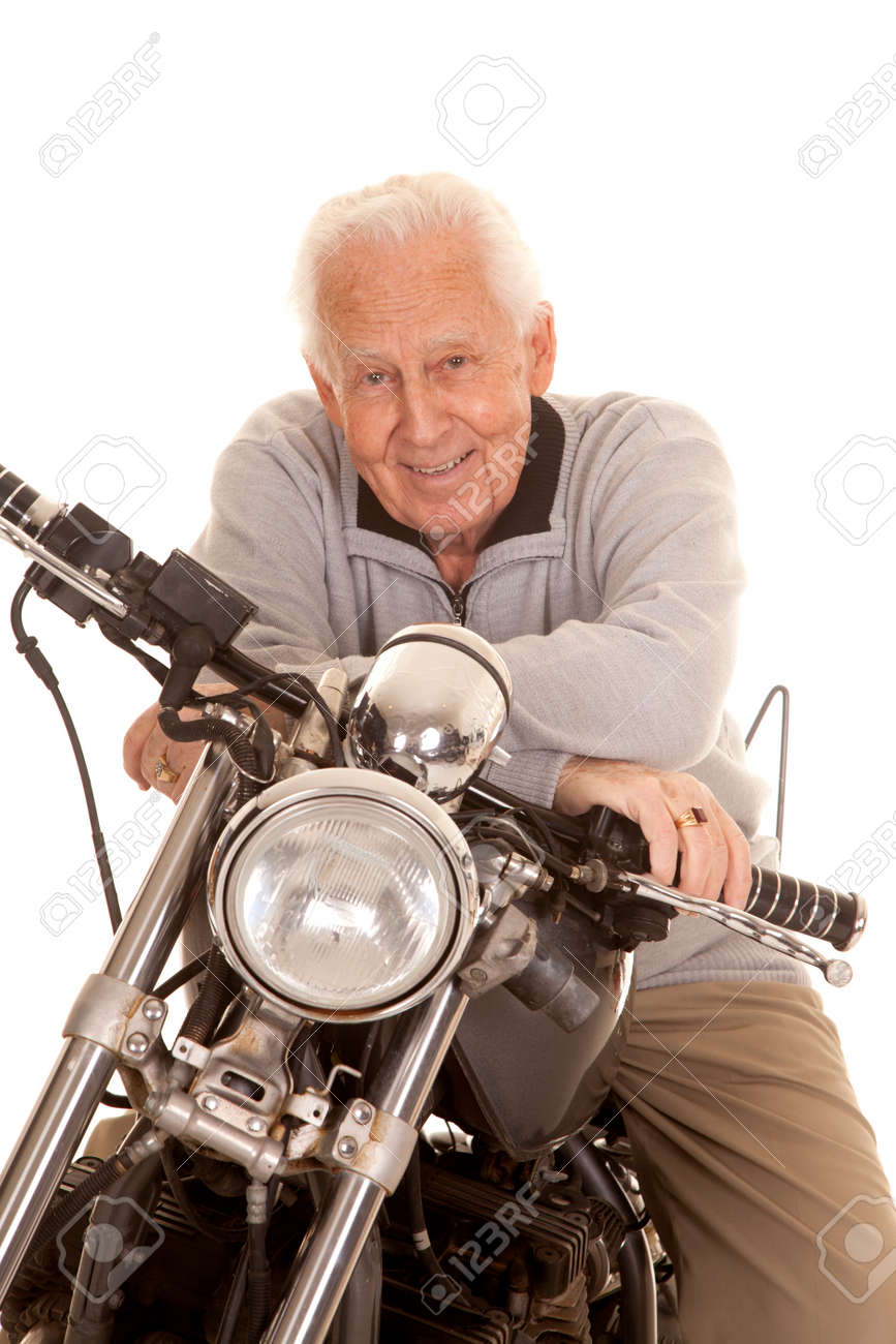 An elderly man sitting on a motorcycle smiling. Stock Photo - 25989854