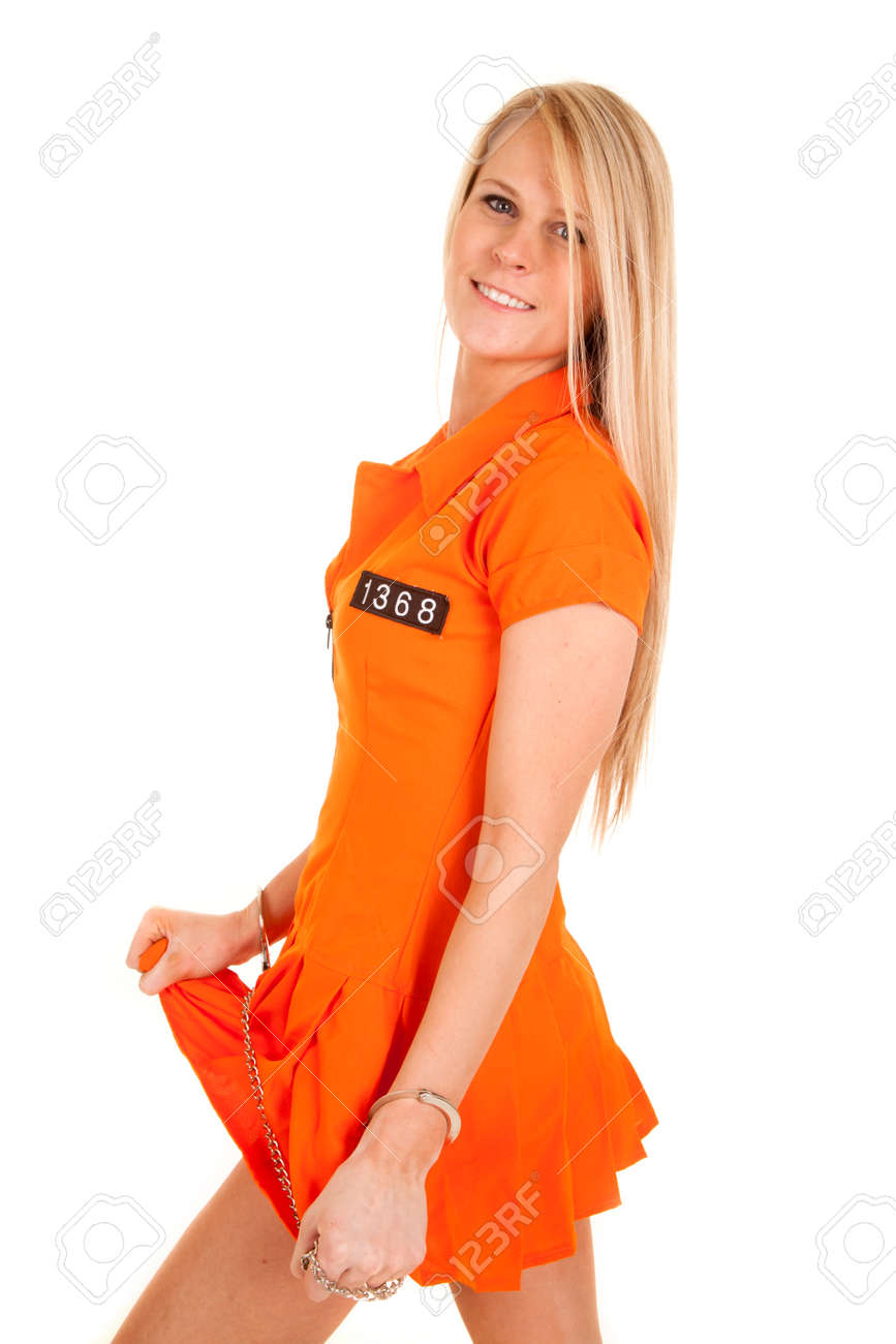 A Woman In Her Orange Jumpsuit Pulling On Her Skirt. Stock Photo ...