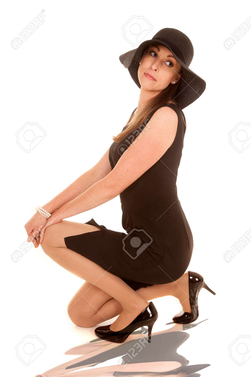 a woman kneeling down in her black dress and black floppy hat stock