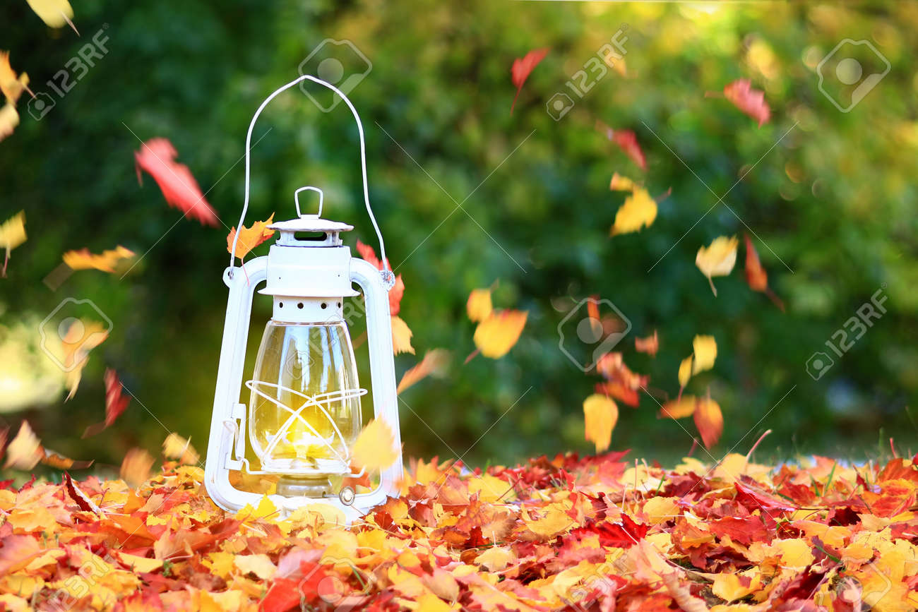 Autumn Leaves Blowing In The Wind Across A Burning Lantern Stock Photo Picture And Royalty Free Image Image 88570374