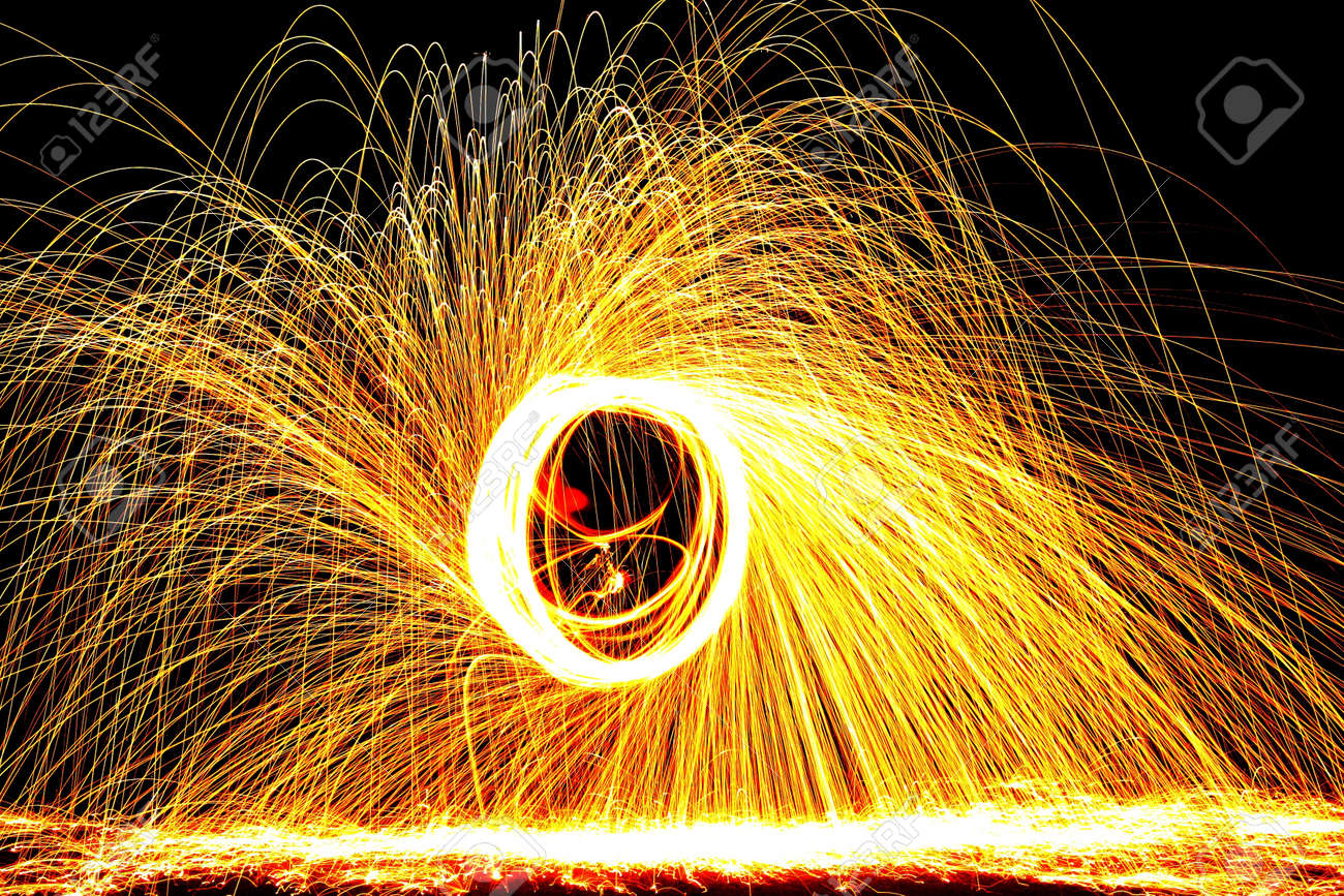 Ignited steel wool spun around forms a circle and releases sparks Stock Photo - 20987154