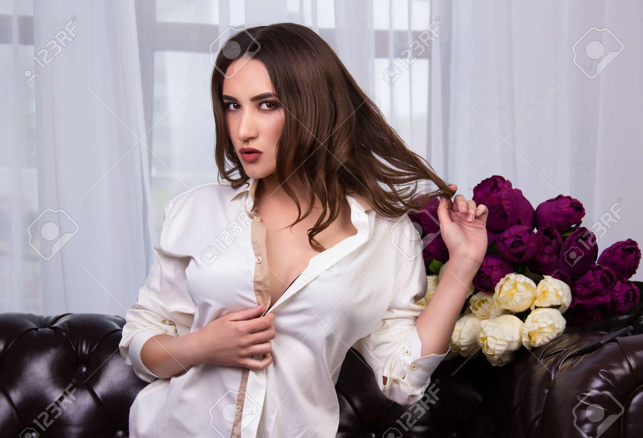 a7cd4f714 Foto de archivo - Mujer joven atractiva en una camisa blanca en un sofá de  cuero. Mañana romántica. Muchacha encantadora que presenta en el sofá en la  ...