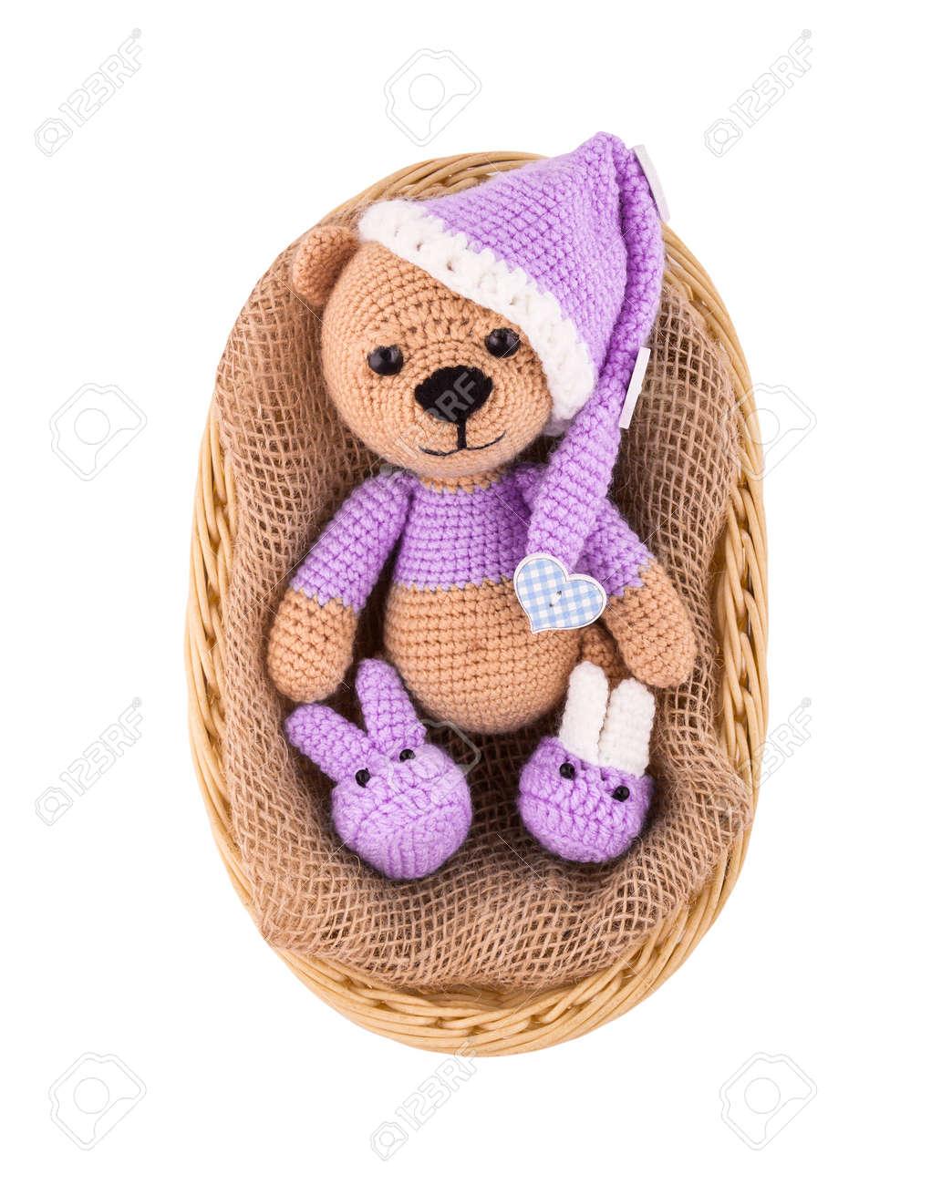 A small knitted teddy bear in a wicker basket  A sleepy bear