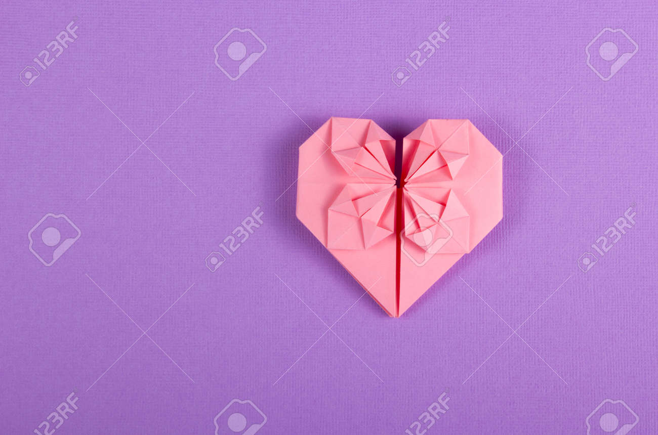 Pink Valentine origami on a lilac background  Heart of paper