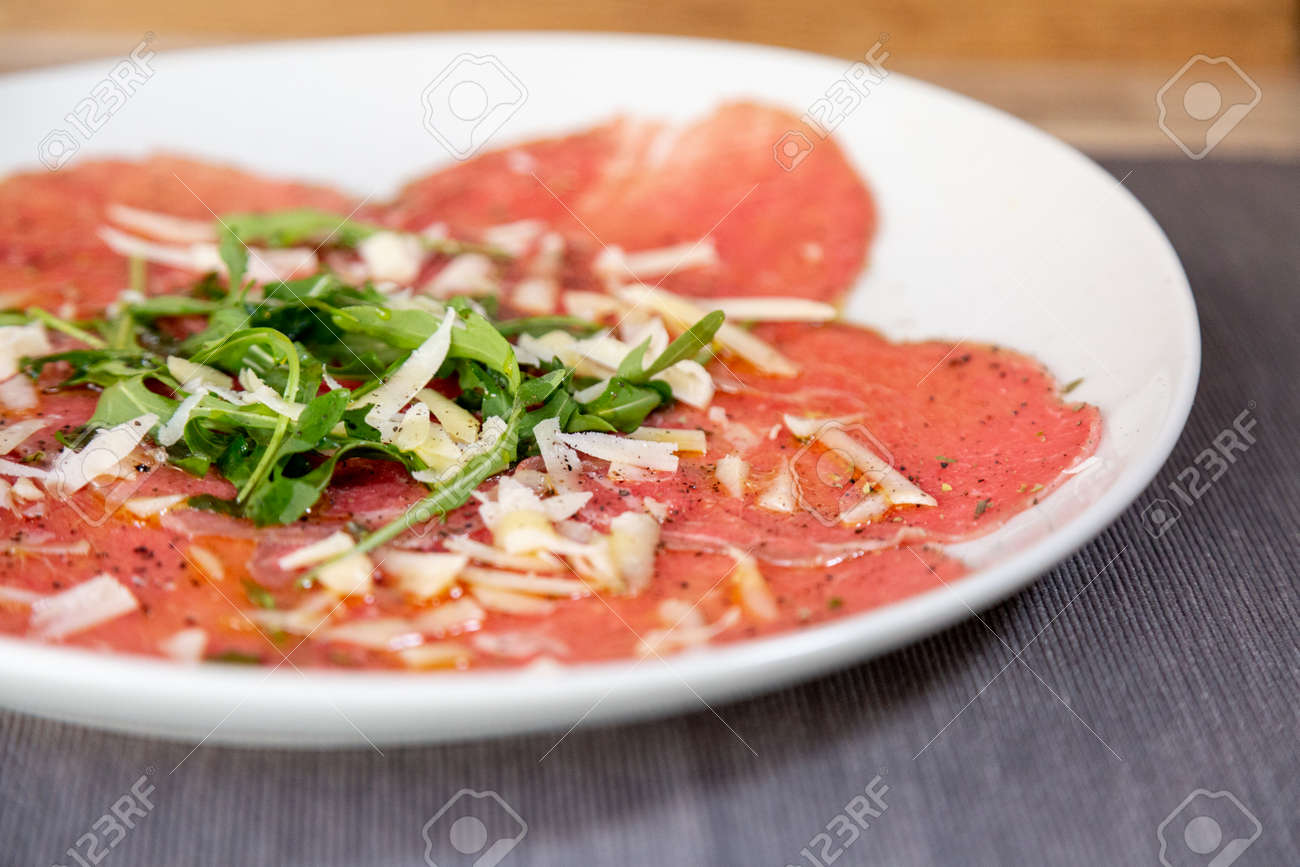 Close up of carpaccio meat with parmesan cheese and arugula in a white plate on a wooden table. With olive oil. - 111866988