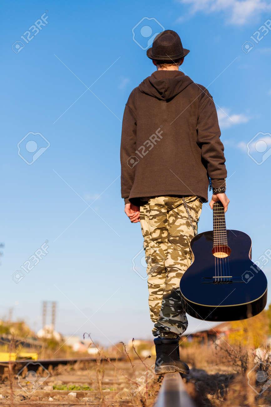 el hombre joven que sostiene la guitarra en sus manos est caminando sobre una ruta de