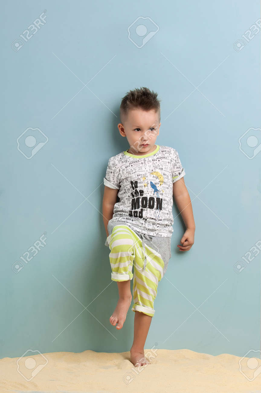 be5541163 little boy in shorts and t-shirt standing on the sand on a light blue