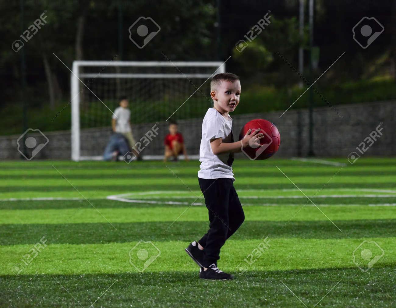 Nino Activo Esta Jugando Con Una Pelota Roja En El Campo De Futbol