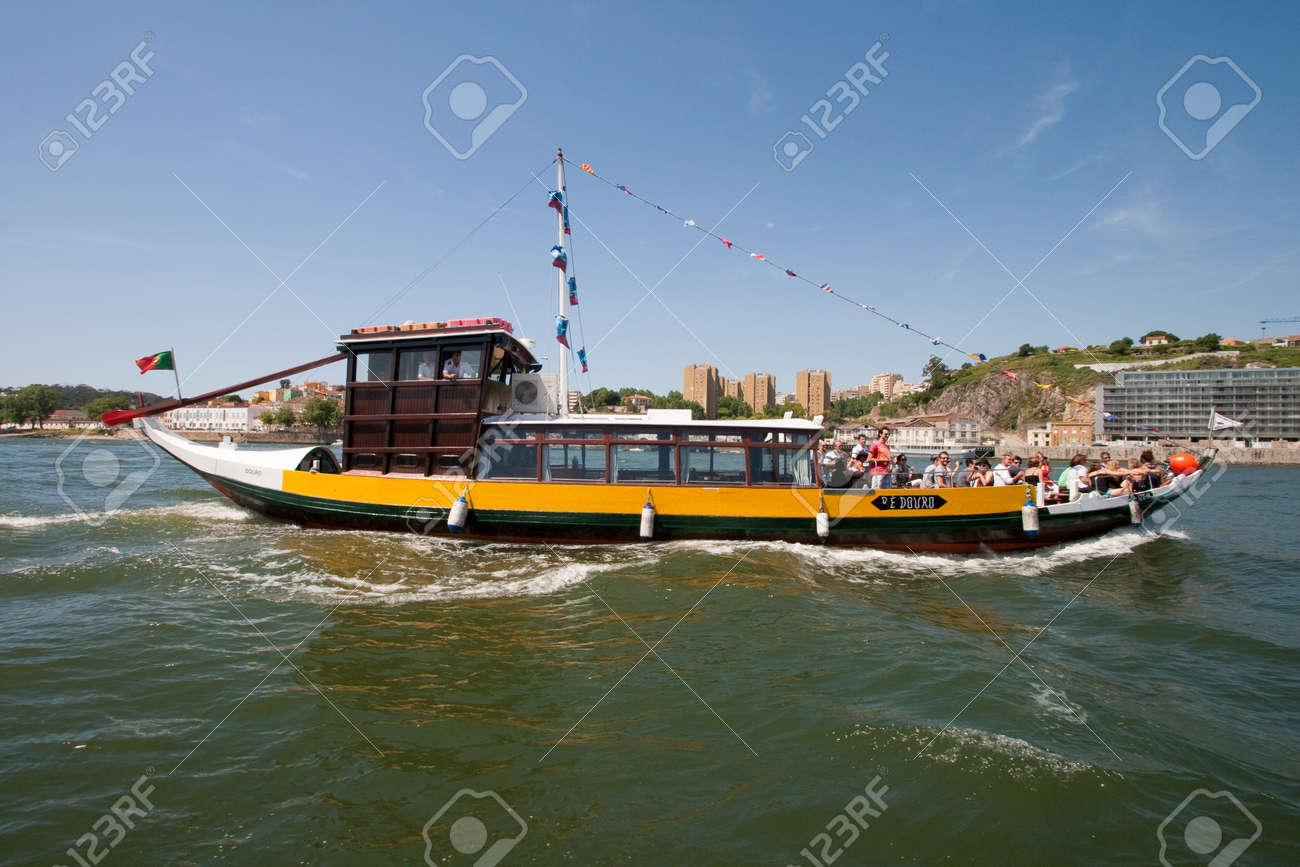 Porto, Portugal - May 14, 2011: Changed Rabelo ship carrying tourists between the bridges of the river Douro showing the riverside area of Porto and Vila Nova de Gaia. Stock Photo - 12271704