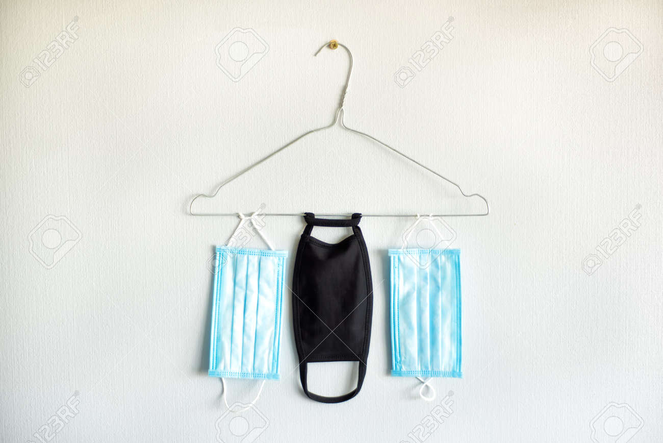 Three medical masks on hanger. Casual outfit in quarantine time. Two casual blue surgical medical mask and one black evening gown mask. Fashion in quarantine. Pandemic concept. - 144303712