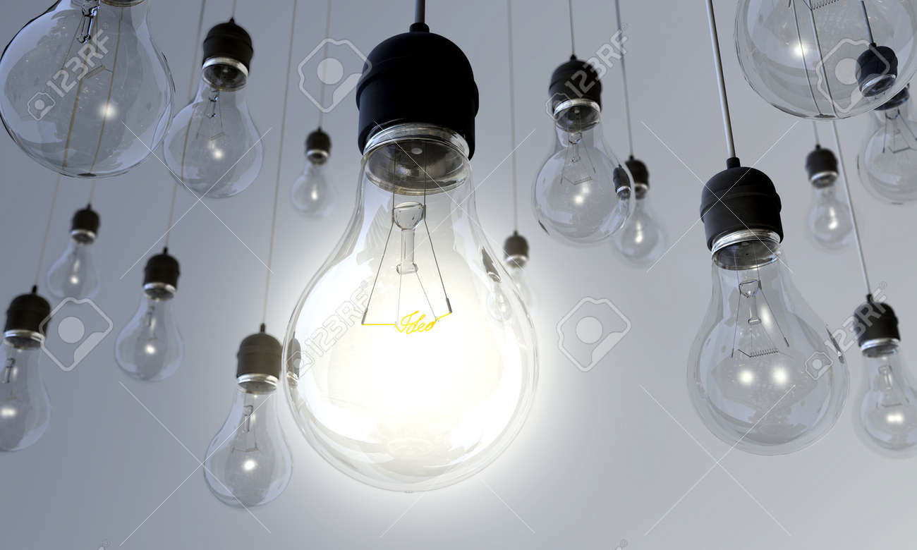 switched on an array of hanging light bulbs with the main one turned on stock
