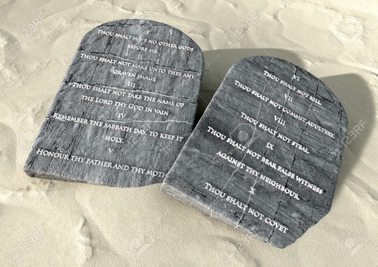 Two Stone Tablets With The Ten Commandments Inscribed On Them Lying On  Brown Desert Sand Фото