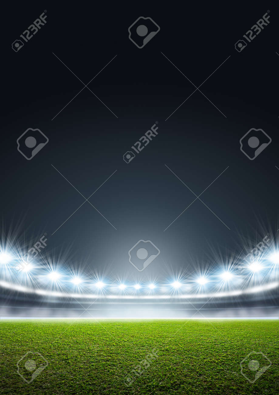 A generic stadium with an unmarked green grass pitch at night under illuminated floodlights - 55276834