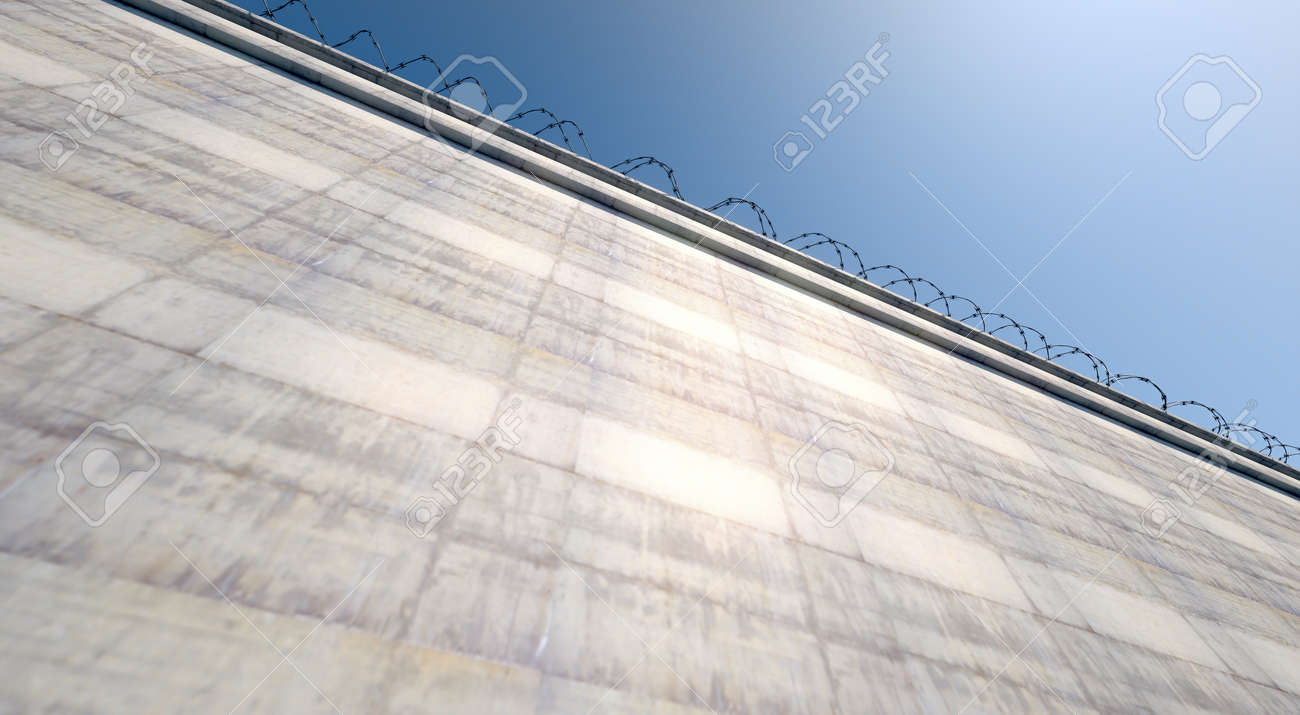 A 3D render of a massively high concrete security wall topped with barbed wire on a blue sky background - 70822075