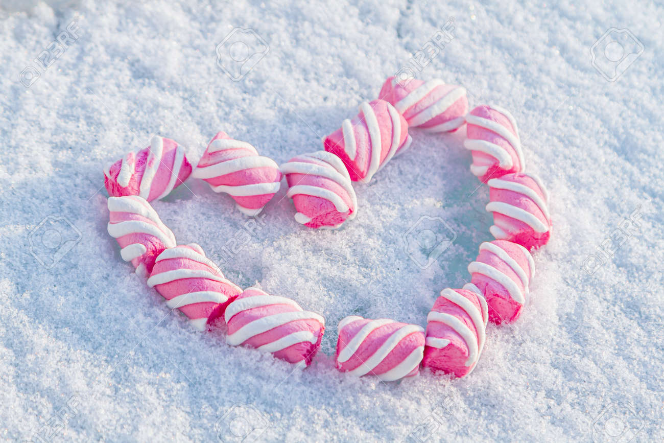 Heart made of marshmallows in the snow. Red heart on a white background. Valentine's Day. Sweets as a gift. Romantic background for Valentine's Day - 163277366