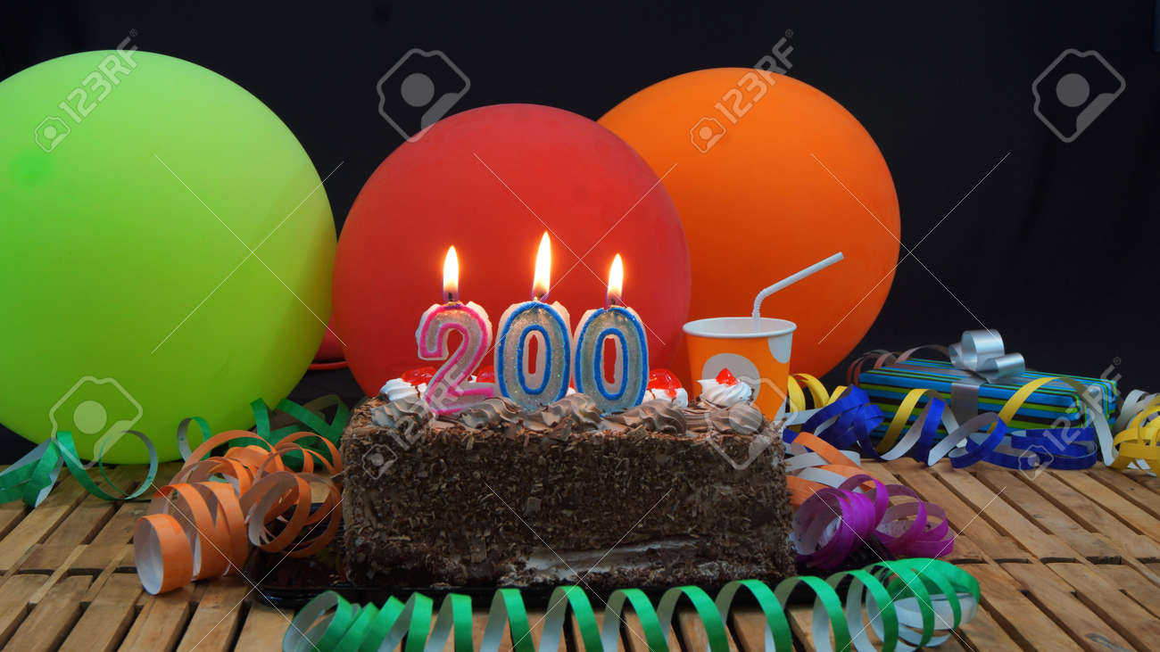 Chocolate birthday cake with candles burning on rustic wooden table with background of colorful balloons, gifts, plastic cups and streamers with black background - 68820939