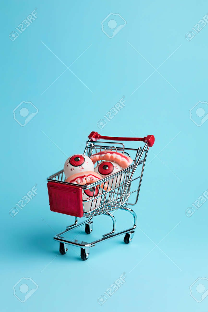 Creative layout made with eyeballs in shopping cart. Minimal Halloween shopping background. Invitation card, party, copy space. - 157117758