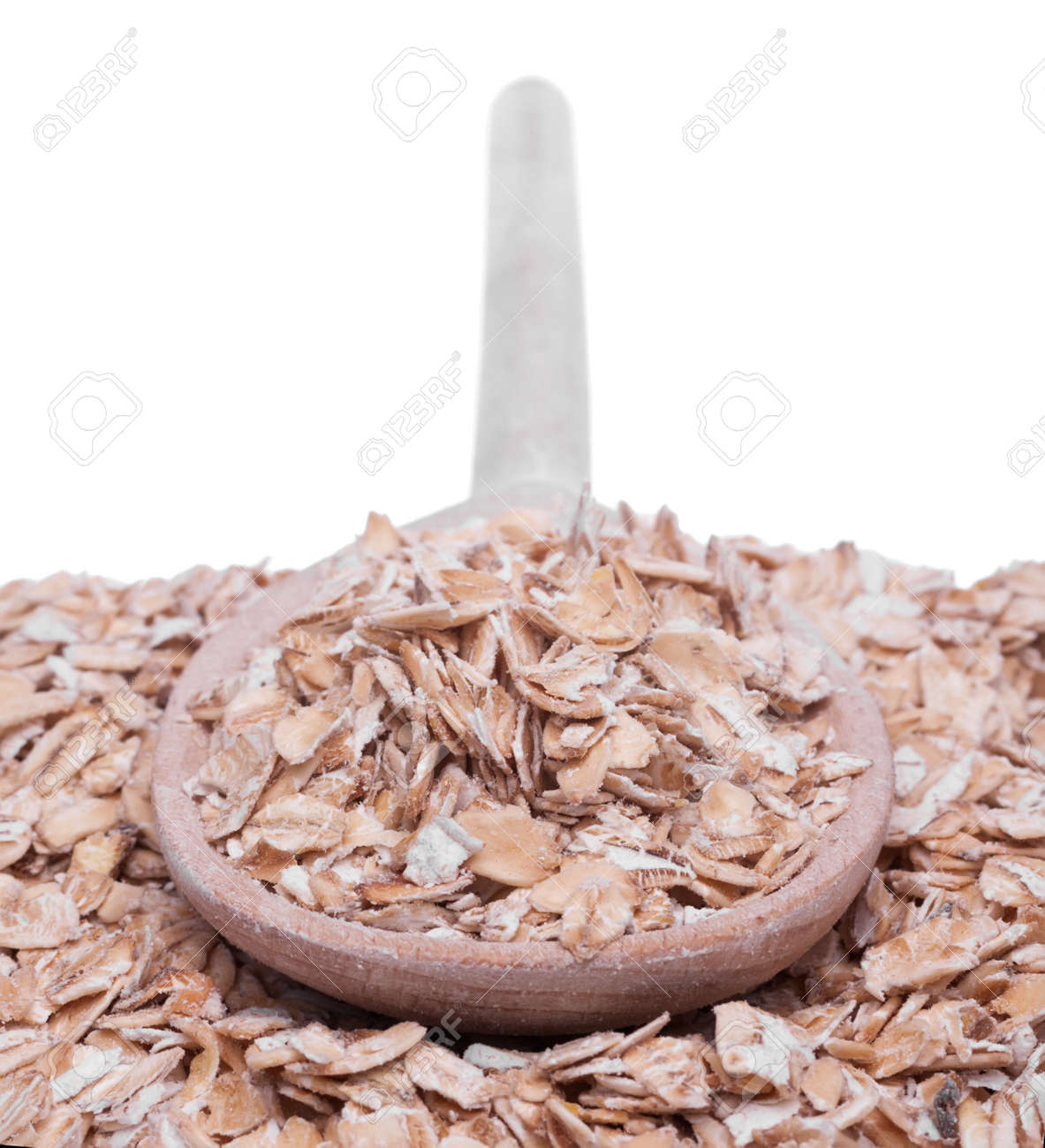 Wooden spoon with oat flakes  isolated on a white Stock Photo - 17589957