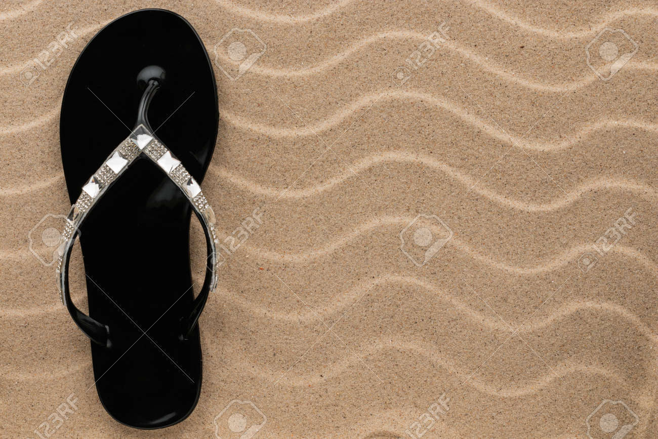 a7aeafe55745 Black Flip Flops With Rhinestones On The Wavy Sand With Place