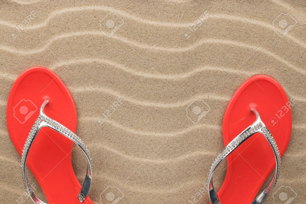 e2ada9159514 Couple beach red flip flops encrusted with rhinestones standing on the  sand