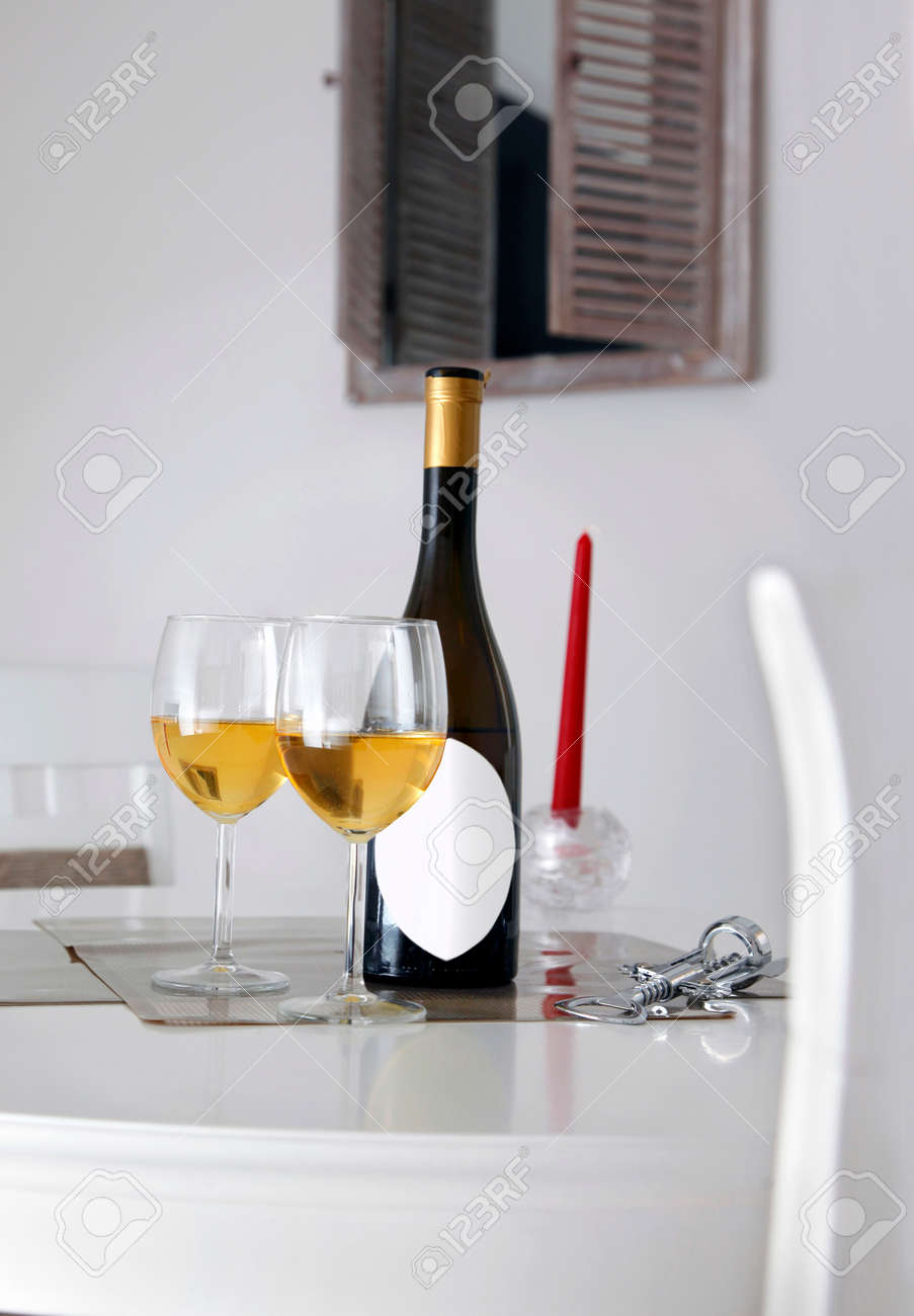 Bottle of wine with white label for caption, opener, two glasses of white wine on table and window in background - 150328695