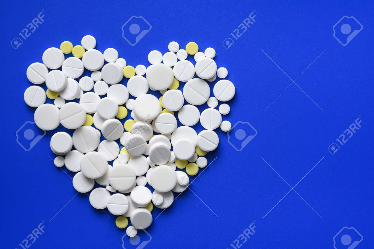 Round tablets arranged abstract isolated on blue color background. Pills for design. Concept of health, healthy lifestyle. Copy space for advertisement. Pills heart shape - 102999952
