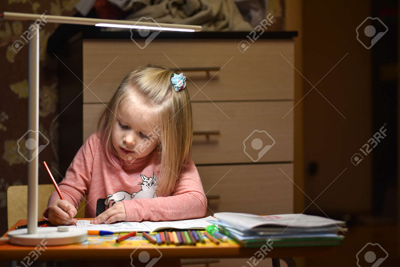 Child preschooler learns to draw and write in notebooks at home in the evening under the light from desk lamp - 118424085