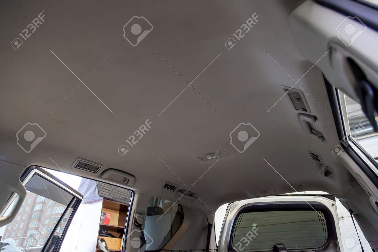 Light beige ceiling in the cabin of the SUV after dry cleaning and seasonal inspection in the workshop for repair and maintenance of vehicles. - 114358426