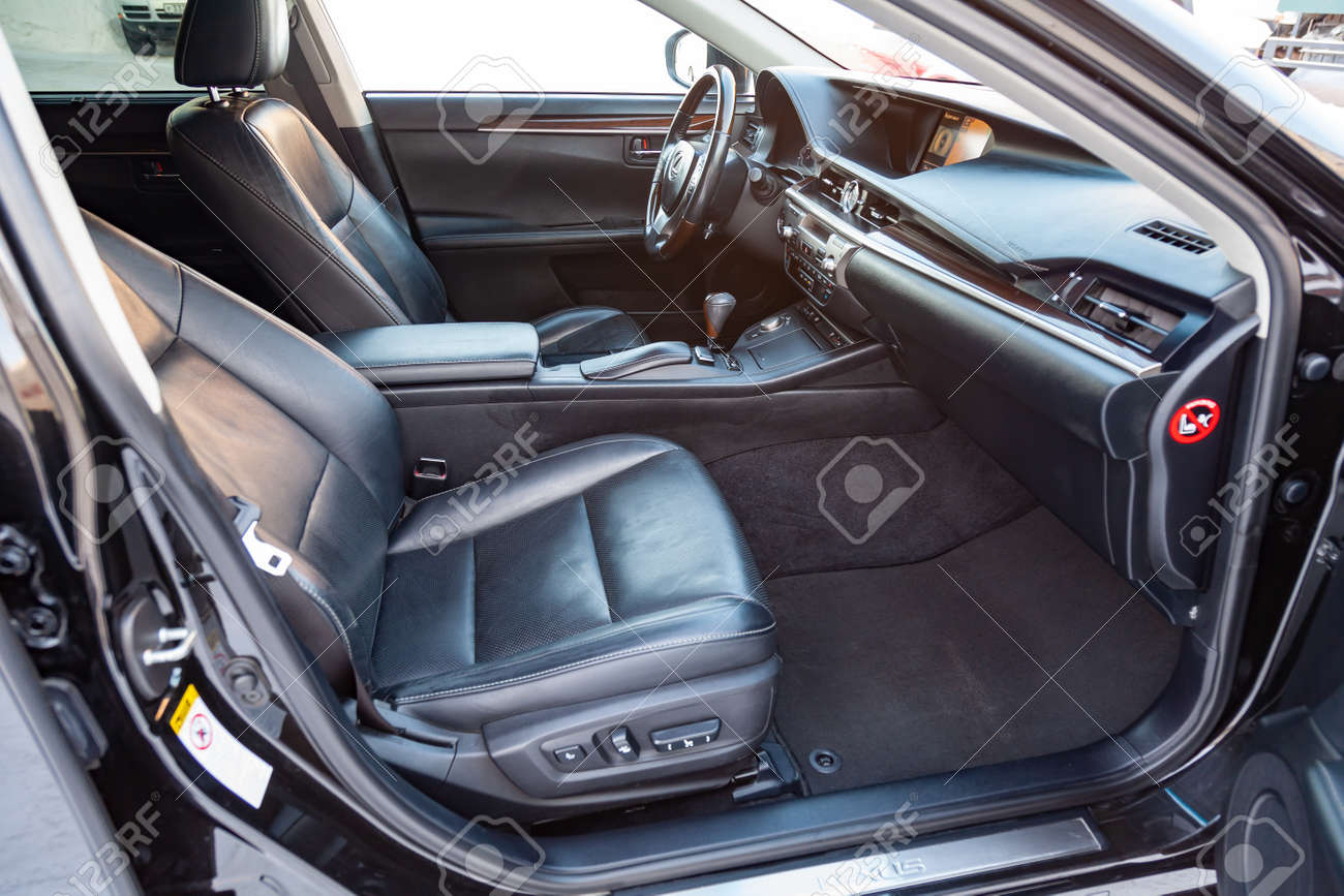 Interior inside the car: front passenger seat, overwhelmed with genuine black leather, modern interior design with wood elements, luxurious central control panel. - 114358772