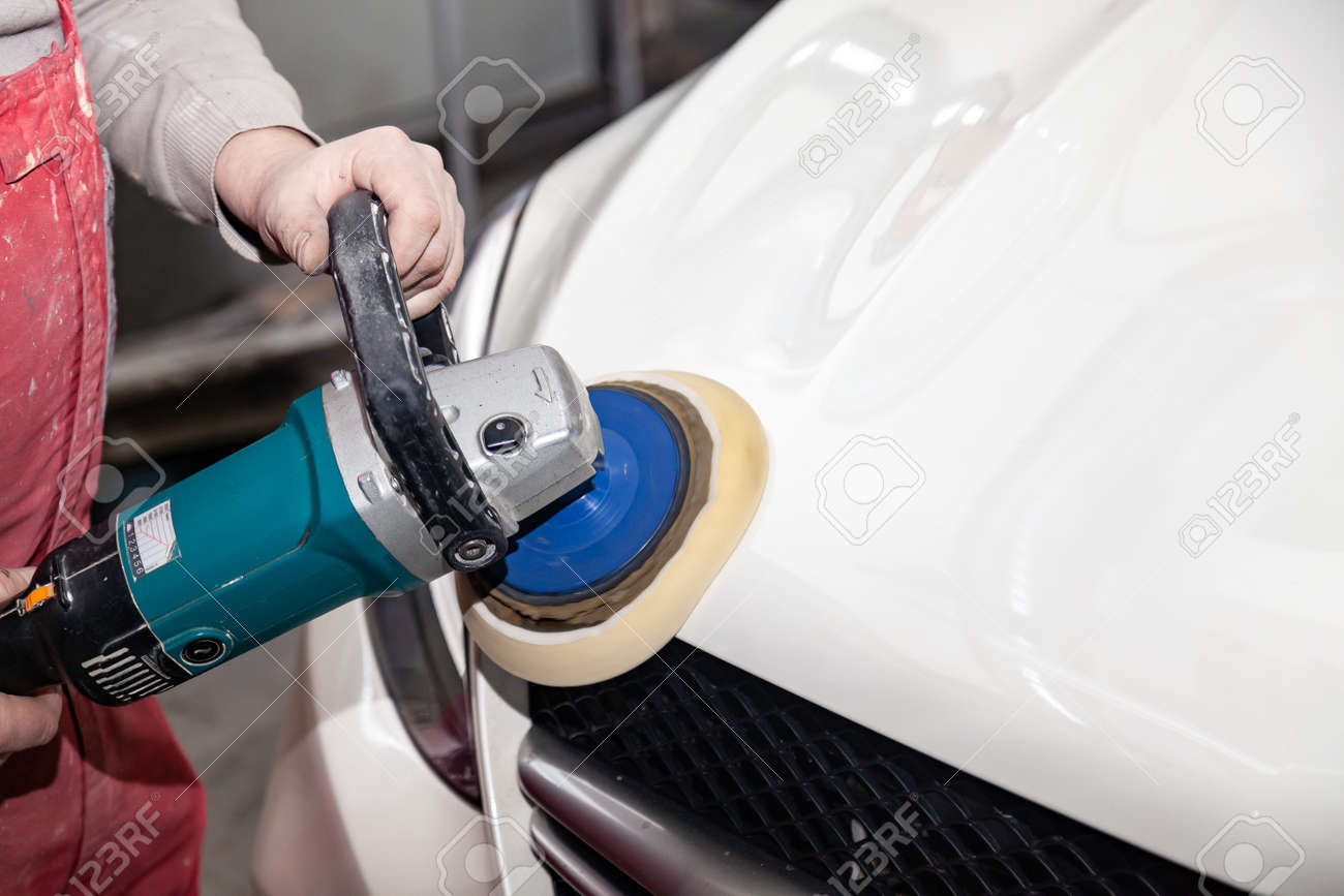 The master man of the detailing in work clothes and dirty hands polishes the bodywork of the bonnet of the car in white with a polishing machine in the workshop for body repair cars - 118411915