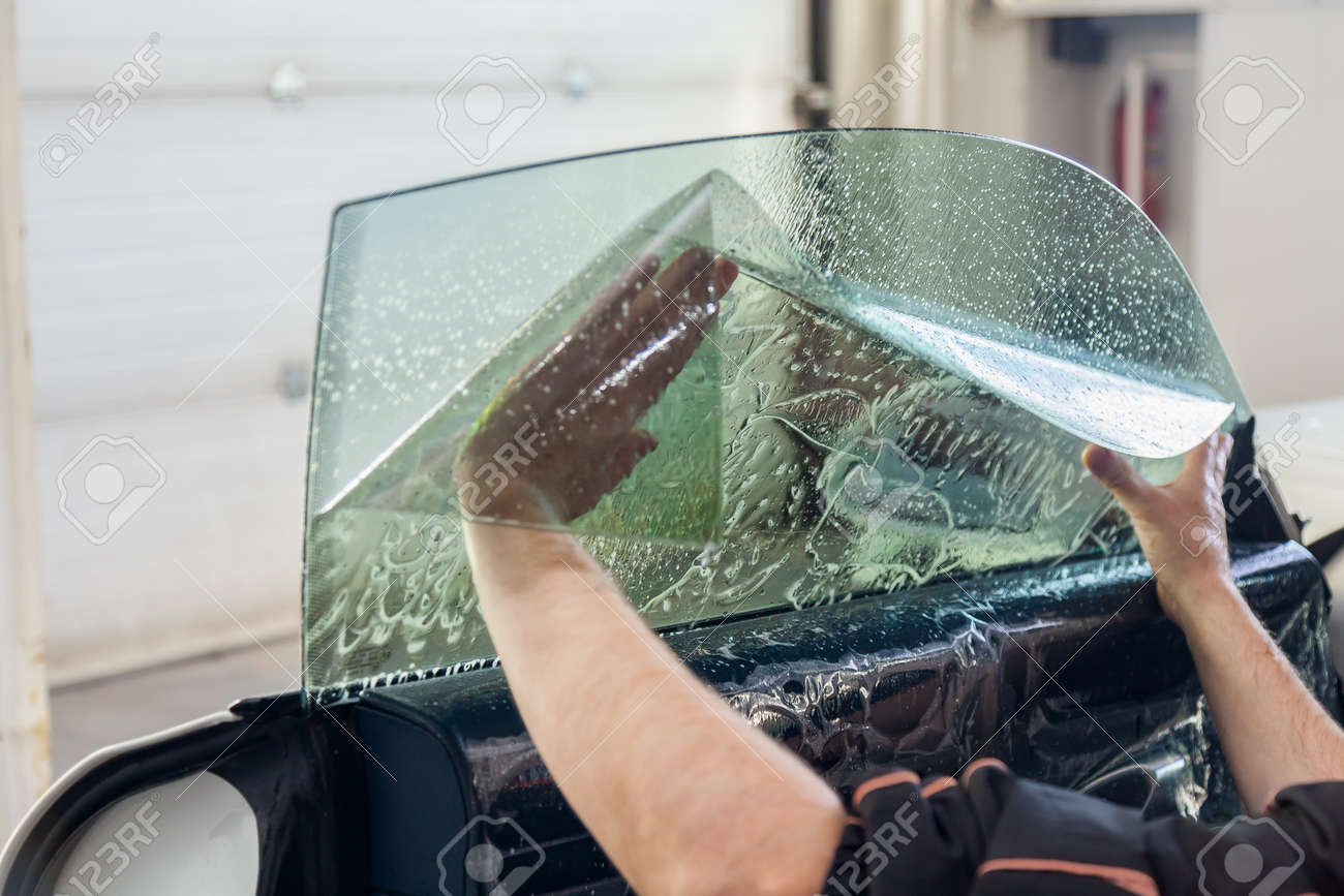 The wizard for installing additional equipment sticks a tint film on the side front glass of the car and flattens it by hand to fit the glass with a greenish tint in the auto service. - 119144410